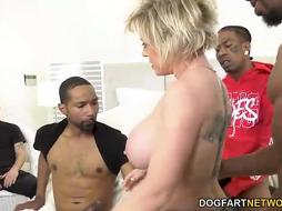 Dee is deepthroating and pawing many dark-hued weenies, one after the other, in front of her accomplice