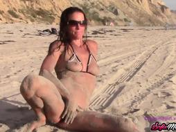 Smoking steaming cougar is posing in a swimsuit and entirely bare, on the beach, during the day