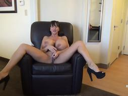Busty woman is wearing nothing but high heels while playing with her dripping wet pussy