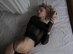 European female is posing in front of the camera and leisurely taking off her softcore underwear